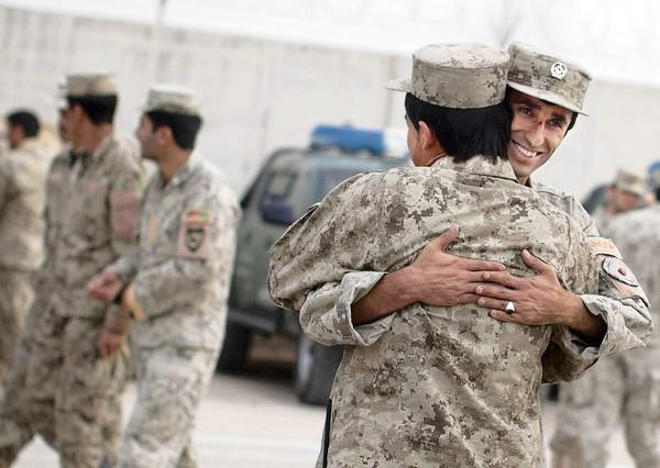 Afghan national policemen embrace each other after a morning drill Oct. 18 at their base in Lashkar Gah, in Afghanistan'sHelmand Province.