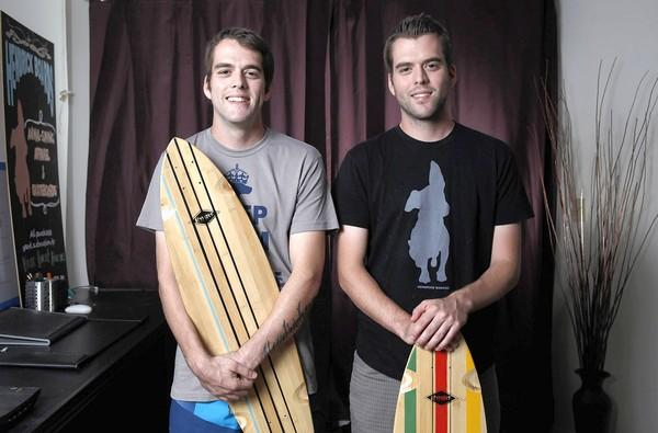 Donny, left, and David Hendrickson, co-founders of Hendrick Boards, are photographed with two of their skateboard decks in David's apartment, which also doubles as their office.