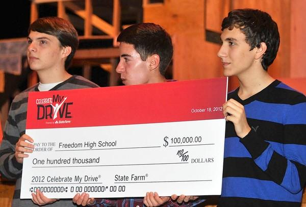 Freedom High School students sophomore Ben Adams (left) 16; senior Lex Donatelli, 18; junior Daniel Youngelman, hold a check for 100,000.00 dollars from State Farm.