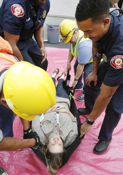 7th and 8th grade English teacher Elizabeth Curtis is loweed onto the red tarp by Pasadene firemen and volunteers during an emergency drill after an earthquake for the Great Shakeout at Pasadena Christian School on Thursday, October 18, 2012.