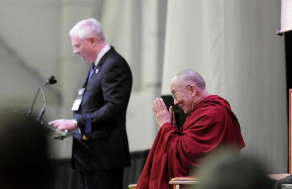 The Dalai Lama bows to the audience as WCSU President Dr. James W. Schmotter (left) makes welcoming remarks at the O'Neill Center at Western Connecticut State University Thursday afternoon. Actor Richard Gere, who introduced His Holiness, is at right.