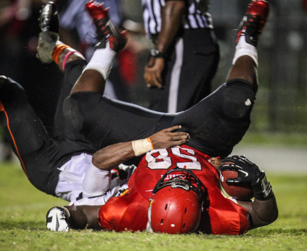 Edgewater's David Green (58) plows through Oviedo's Justin Spencer (6) to score a touchdown during second quarter action of a high school football game against Oviedo in Orlando, Fla. on Thursday, October 18, 2012.