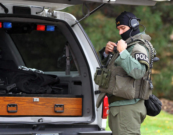 A member of the Northern Illinois Police Alarm System readies his equipment at the scene of a standoff between police and a man barricaded in a house in Gurnee.
