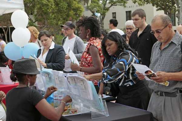 People look for jobs at the Los Angeles World Airports booth during a job fair at Los Angeles City College.