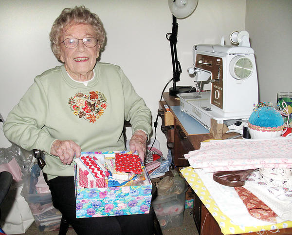 Angie Supernaw sits at her sewing table in her apartment at Sunnybank Assisted Living where she recently made 17 dresses for children in Africa.