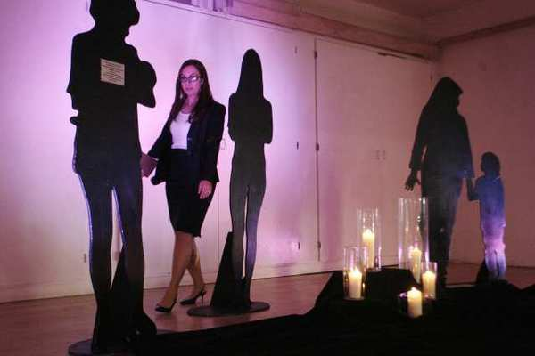 Christine Powers rearranges the silhouette figures before a candlelight vigil for victims of domestic violence, which took place at YWCA in Glendale.