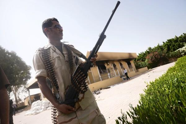 A member of the Libyan security forces secures the area during a visit by the head of Libya's national assembly, Mohammed al-Megaryef, to the US consulate compound in Benghazi on September 14, 2012 to pay  respects to slain US ambassador Chris Stevens who died earlier this week when suspected Islamic militants fired on the compound with rocket-propelled grenades and set it ablaze.