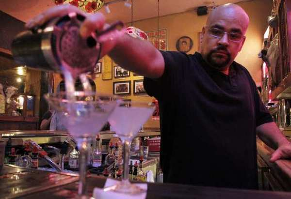 Bartender Jesus Gamboa stays busy serving a clientele that has seen the neighborhood grow more upscale through the years.
