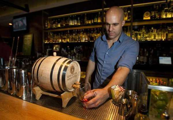 Mess Hall Kitchen bartender Erik Lund pours a barrel-aged Smith & Cross Jamaican rum, which has a proof of 114.