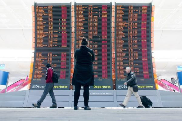 Travelers pass by a board announcing flights canceled as the result of a cloud of volcanic ash from Iceland at the Roissy Charles de Gaulle Airport near Paris in 2010.