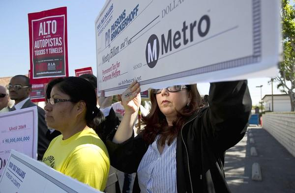 Lisa Korbatov, right, and Rosa Miranda of the Bus Riders Union hold up blank checks in an effort to highlight Measure J's corporate sponsors and beneficiaries.