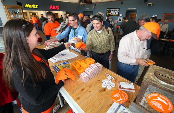 Heidi Appel, with the Aberdeen Convention and Visitors Bureau, left, hands out blaze orange caps to the hunters arriving at Aberdeen Regional Airport on Friday. Hunters are flocking to the area for today's opening of the nonresident pheasant hunting season.