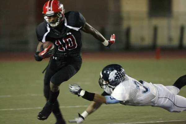 Glendale receiver Michael Davis avoids a Crescenta Valley tackler and heads downfield.