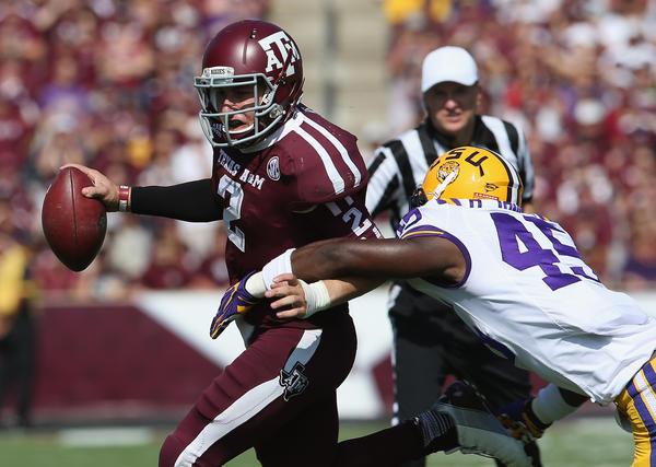 Texas A&M quarterback Johnny Manziel tries to evade LSU linebacker Deion Jones on Saturday.