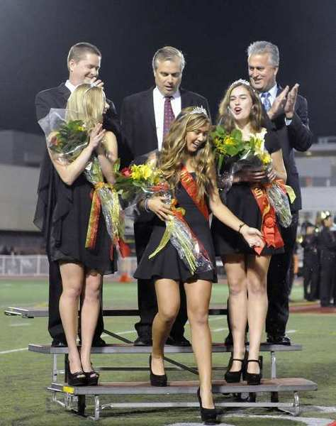 Rick Gunter and his daughter Hannah, left, Scott Monroe, center, and Jim Young and his daughter Amy, right, congratulate Annie Monroe as she is named Homecoming Queen during halftime of a Rio Hondo League prep football between Sough Pasadena and La Canada at La Canada High School.