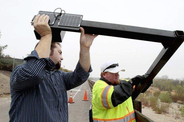 Dave Mickey, left, Cal Arts adjunct professor, and Warren Griffiths with the city of Santa Clarita install one of the sound devices along the South Fork Trail.