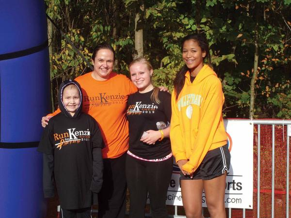 Melissa McCarter and her daughter, McKenzie McCarter, 9, of Hagerstown, pose with Brett Jamison, 17, and Noelle Seals, 15, both of Hagerstown, who came out to support the McCarter family Saturday at the Run for Kenzie 5K Run and Walk at Antietam National Battlefield.
