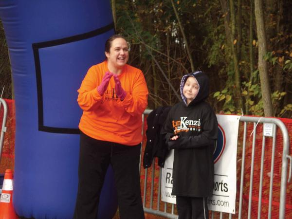 Melissa McCarter and her daughter, McKenzie McCarter, 9, of Hagerstown, cheer participants past the finish line Saturday at the Run for Kenzie 5K Run and Walk at Antietam National Battlefield.
