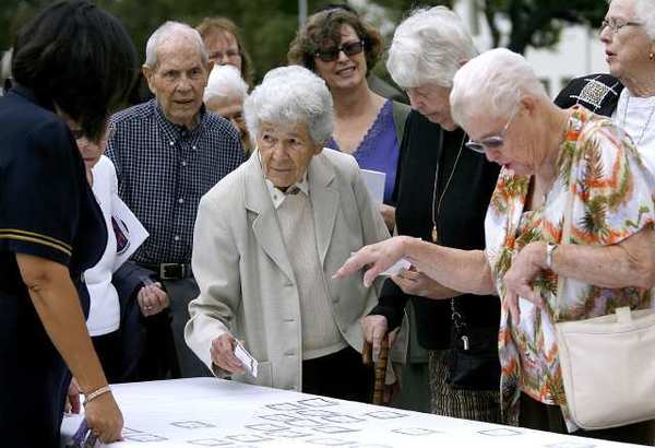 Sister Mary Jean ferry, class of '52 and 78 years old, at center with name tag in hand, checks in at the Holy Family High School 75th Anniversary Celebration on school grounds in Glendale.