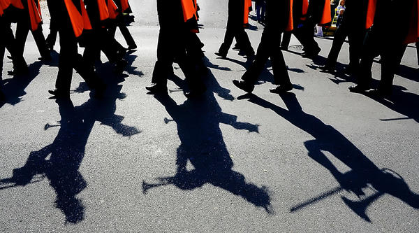 Shadows are cast on King Street as The Martinsburg High School Marching Band marches in the Mountain State Apple Harvest Festival parade Saturday.