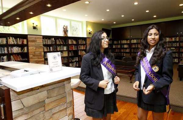 Marisela Avendano, left, and Angelica Rodriguez, right, both juniors, give tour of the facilities, including the school's library, during the Holy Family High School 75th Anniversary Celebration.