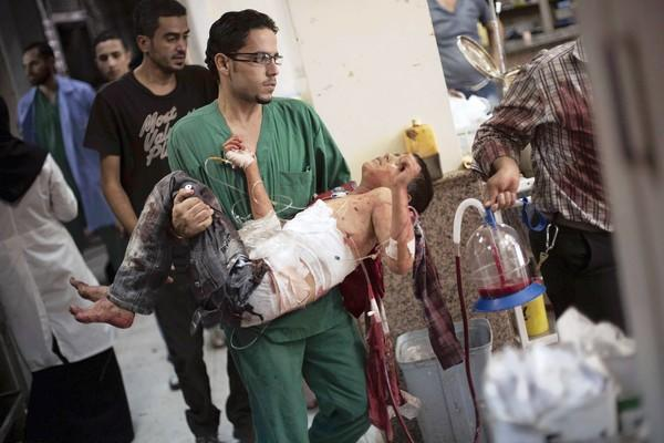 A doctor carries a badly wounded boy in a hospital in Aleppo, Syria.