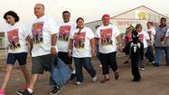 Cancer survivors and supporters walk around the field