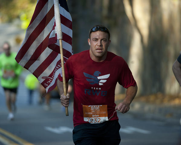 John Kline of Oaklyn, New Jersey, holds a flag as he moves with runners along Illicks Mill Road in Bethlehem, during the Runner's World Half Marathon on Sunday. The 13.1-mile course wound through Bethlehem¿s historic neighborhoods, Lehigh University and Moravian College), and the former Bethlehem Steel complex.