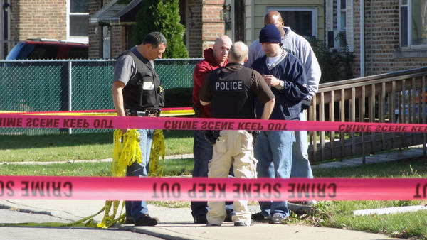 Chicago police respond to a shooting at the intersection of 98th Street and Merrill Avenue on Sunday. Authorities say an officer shot a gunman after that person exchanged gunfire with officers.