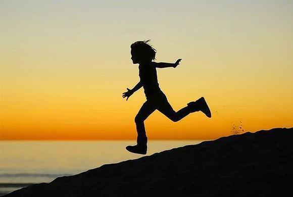 A boy runs down a sand dune while playing after the sun sets at Moonlight Beach in Encinitas