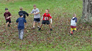 A group of young boys play touch football in Shirley, Mass.