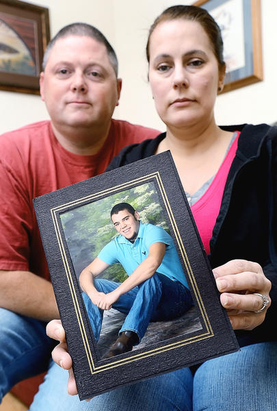 Cody E. Butz's stepfather and mother Stephen and Carin Trecannelli are shown at their Hagerstown home with one of Cody's senior portraits.