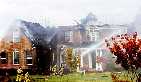 Firefighters battle a house fire at the Ridges of Tuscarora development off Lost Road west of Martinsburg, W.Va., on Sunday.