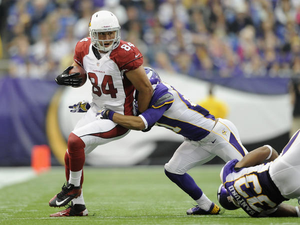 Josh Robinson #21 of the Minnesota Vikings tackles Rob Housler #84 of the Arizona Cardinals during the fourth quarter of the game on October 21, 2012 at Mall of America Field at the Hubert H. Humphrey Metrodome in Minneapolis, Minnesota. The Vikings defeated the Cardinals 21-14.