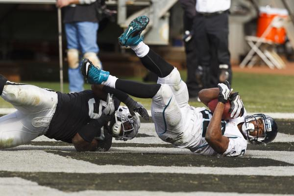 Running back Rashad Jennings #23 of the Jacksonville Jaguars is tackled for a loss by defensive end Lamarr Houston #99 of the Oakland Raiders during the third quarter at O.co Coliseum on October 21, 2012 in Oakland, California. The Oakland Raiders defeated the Jacksonville Jaguars 26-23 in overtime.