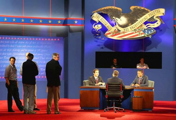 Stand-ins for President Obama and Mitt Romney sit at a debate table at Lynn University in Boca Raton, Fla., at a reshearsal for Monday night's third and final presidential debate.
