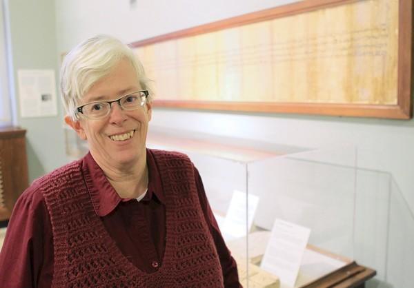 University of Chicago scholar Janet Johnson, at the Oriental Institute on campus, poses with an ancient Egyptian marriage contract on the wall. Her 37-year research project on demotic Egyptian led to a large dictionary of everyday language from ancient times.