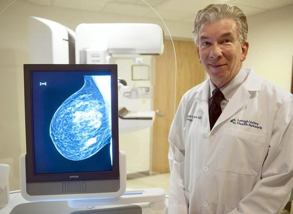 Dr. Kenneth Harris, director of breast imaging at Breast Health Services, shows the image from a new 3-D scan of a breast. The white masses are likely fibroglandular tissue.