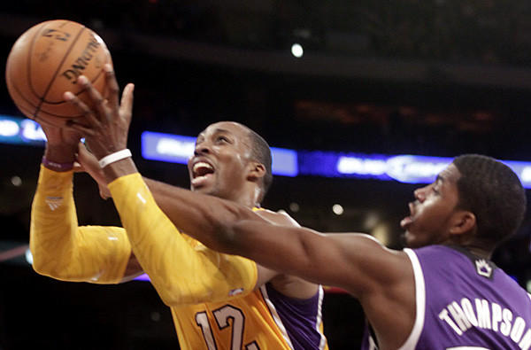 Lakers center Dwight Howard is fouled by Kings power forward Jason Thompson in the first half Sunday night.
