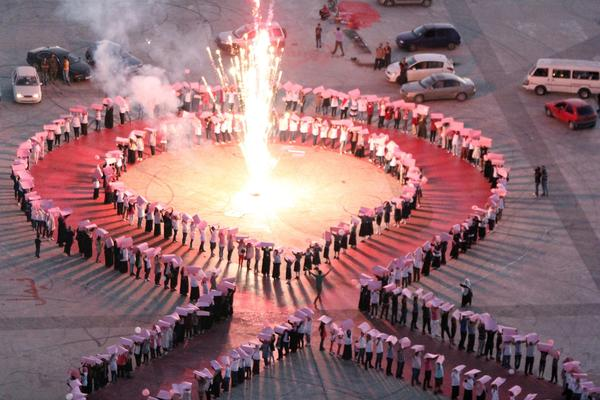 Benghazi residents and activists make a human chain in the shape of a 'pink ribbon', lit by a central firework, during a rally to mark International Breast cancer awareness month, on October 1, 2012, in the Libyan city of Benghazi.