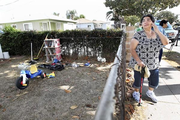 A former neighbor grieves for the victims outside the home in Inglewood.