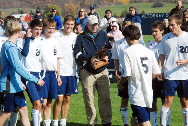 Former Petoskey soccer coach Scott Batchelor (middle) prepares to present the Division II district championship trophy to the Northmen Saturday at the Click Road Soccer Complex. The Northmen defeated Bay City Western, 5-0, to capture it's first district title since 2009.