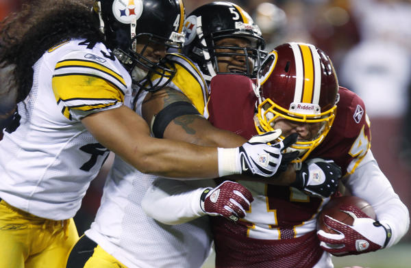 Washington Redskins tight end Chris Cooley, right, is tackled by Pittsburgh Steelers safety Troy Polamalu, left, and linebacker LaMarr Woodley during the fourth quarter of an NFL game on Nov. 3, 2008.