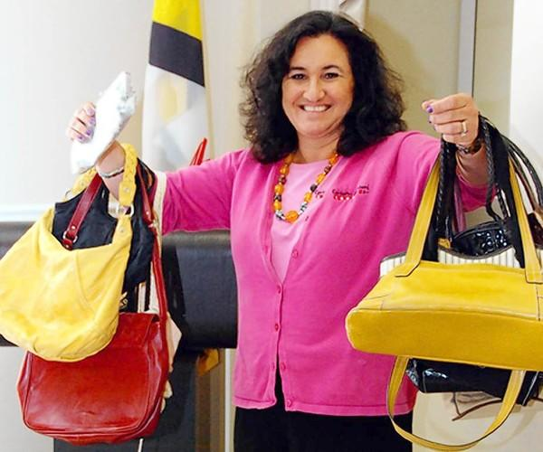 Lorena Streb, a member of the Baltimore County Commission for Women, holds some of the purses that have been donated in advance of the Tuesday, Oct. 23, Power of the Purse event at 7 West Bistro Grille in Towson. The event is a fundraiser for organizations working to raise awareness about the issue of human trafficking.