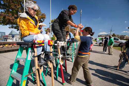 Nan Tuckett, left, of Pigtown, watches Carmen Shorter, of Baltimore City, as she gets help standing up on her stilts from volunteer Jodie Zisow, of Nana Projects.