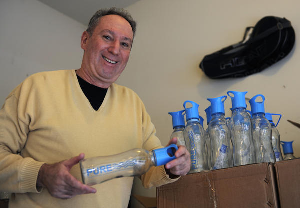 Walt Himelstein is inventor/owner of Pure Glass Bottle, a glass bottle coated with plastic so that if it breaks it will not shatter. He started his company at home and works out of his garage and basement. Here, he holds one of the bottles in his garage, which doubles as a storage area.