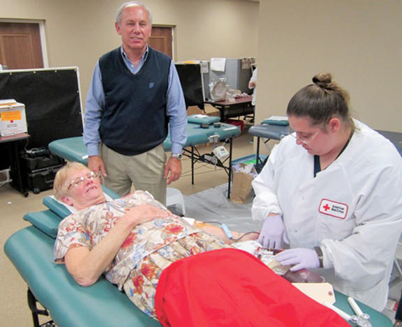 Adele Knott of Shenandoah Junction, W.Va., donates blood Monday under the watchful eye of American Red Cross staffer Rebecca Meeks. Also shown is Lee Snyder, who helped organize the second annual blood drive in memory of his wife, Cynthia Snyder.