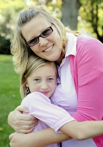 Amanda Buss, 34, hugs her daughter, Madalyn Buss, 9, after she gets off the school bus.