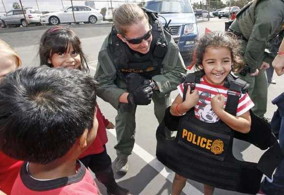 Kayla Zakarian, 6, tries on a bullet proof vest with some help from a DEA agent during a Red Ribbon Week assembly at Mark Keppel Elementary on Monday, October 22, 2012. (Roger Wilson/Staff Photographer)