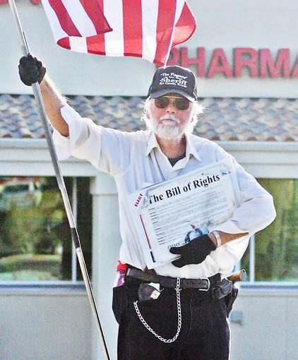 "Ray ""the Flagman"" Mielzynski of Pahrump, Nev., packs two guns and copies of the Bill of Rights that he hands out to passersby. A battle is brewing over proposed cityhood for the unincorporated town."